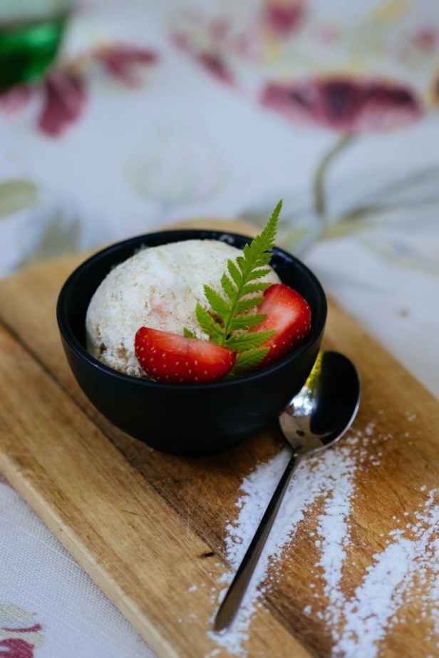 ice cream served on black bowl with spoon